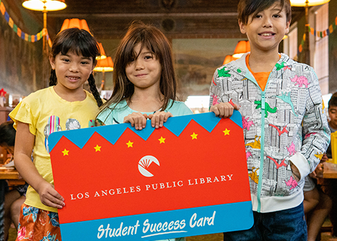 three kids hold a huge student success card