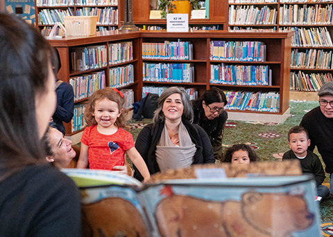 a librarian reads to a group of young kids and their caregivers