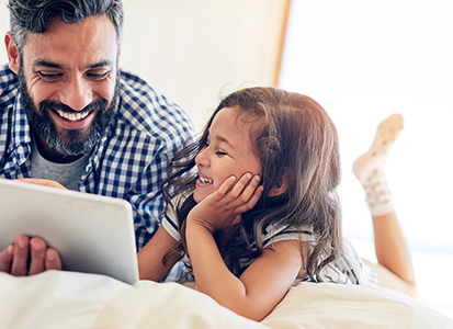 father and young daughter watch content from a tablet