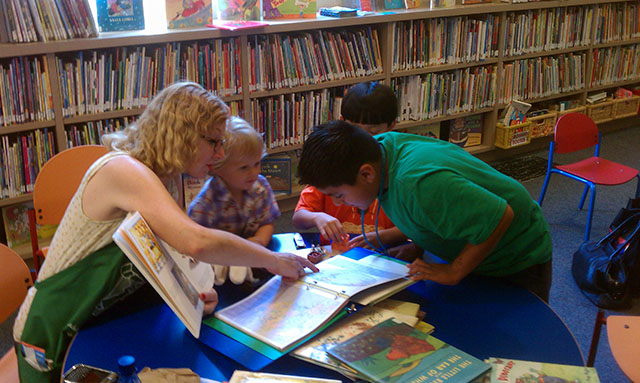 Woman and kids looking at books