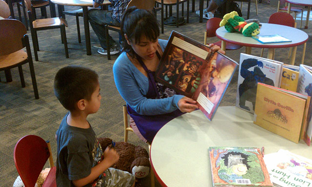 Woman and boy reading a picture book