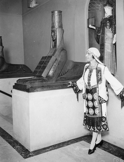 A woman poses with Civilization and one of the sphinxes, 1930.