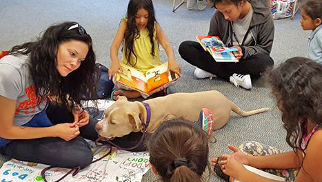 Librarian and kids reading to a BARK therapy dog