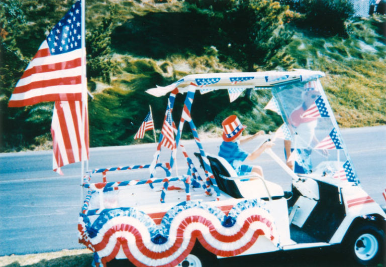 A boy drives a golf cart decorated for a Fourth of July parade in San Pedro.