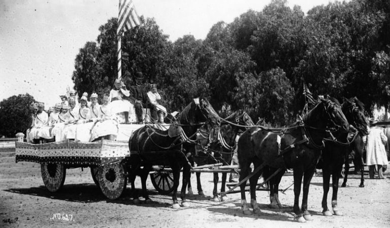 A horse-drawn wagon carries costumed participants in a 4th of July parade in Santa Ana.