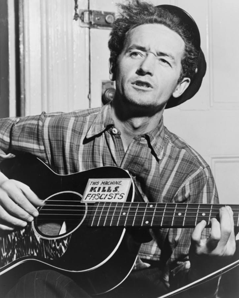 Woody Guthrie, half-length portrait, facing slightly left, holding guitar