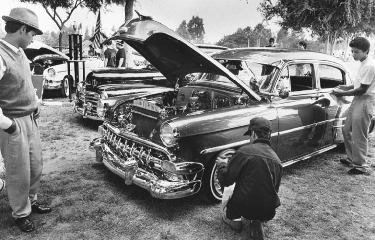 A collection of classic lowrider cars is displayed in Huntington Park for the Fourth of July. (Anne Knudsen/Herald-Examiner Collection, July 4, 1982)