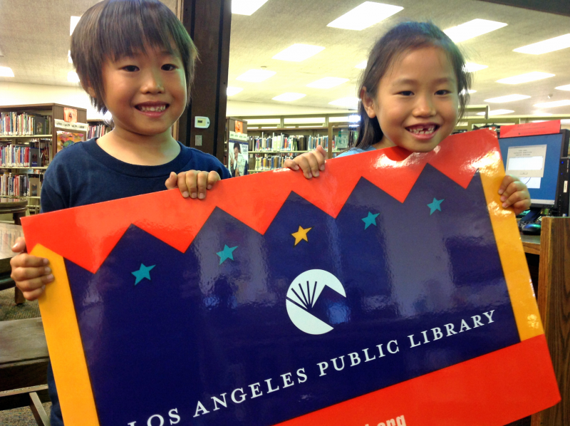Kids hold a huge library card at the San Pedro Library