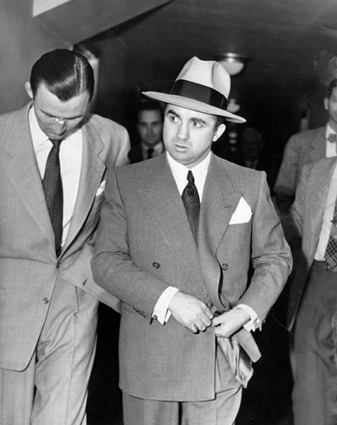 Mickey Cohen, wearing suit, tie and hat, walks indoor with a man walking closely on one side of him, and a group of men following behind.