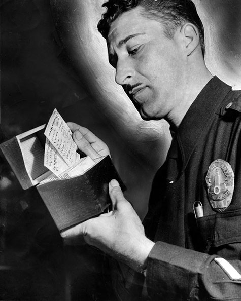 May 8, 1948 reads,Vice Sgt. C. W. Bates examines name-cards