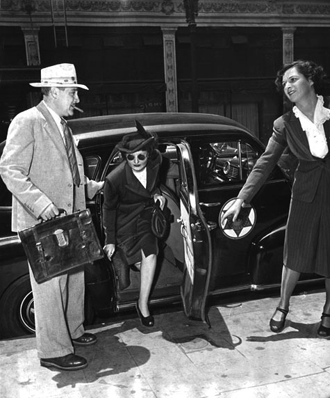 June 16, 1949 Brenda Allen wearing dark glasses, steps from an auto during a tour of deposit box vaults