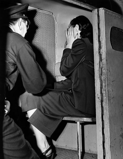 August 11, 1948 With her hand up, apparently to hide an ironically 'shamed' face, Brenda Allen sinks into corner of police patrol wagon