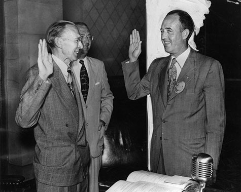 Los Angeles Police Chief William H. Parker raises his right hand (right) and takes his oath of office. The oath is administered by City Clerk Walter C. Peterson on August 9, 1950.