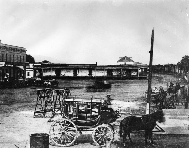 Lafayette Hotel stagecoach near the adobes in Calle de los Negros circa 1870, presently Alameda Street near Union Station and Terminal Annex Building. The old Antonio Coronel adobe is in the background.