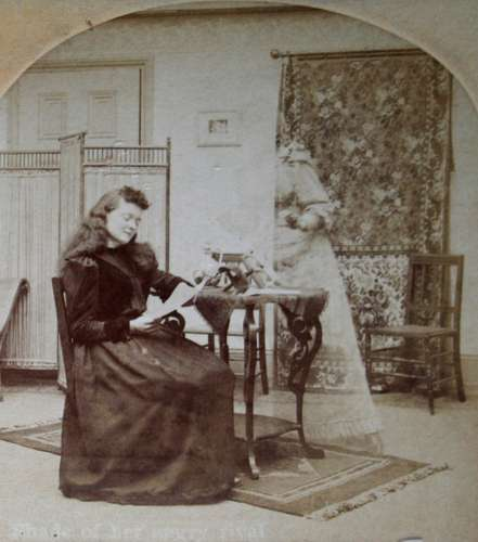 Photograph by William H. Rau (1855–1920) showing a woman reading with a ghostly figure standing over her