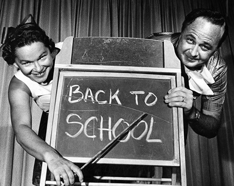 a man and a women point at a back to school sign on a chalk board