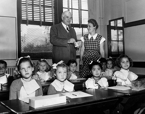 Dr. Alexander Stoddard, new superintendent of schools, and Mrs. Bertha Norton, teacher, look over the first group of children