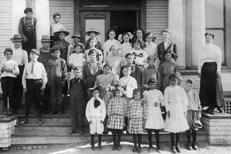 Young students pose for a class photo outside of the wooden schoolhouse of the Lemon School in Puente