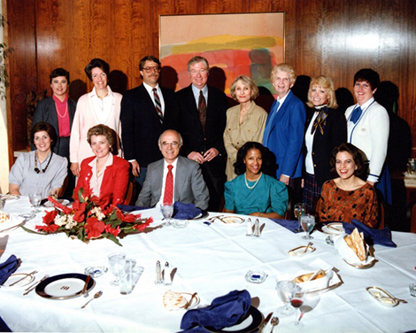 group of people in a wood-paneled room having dinner