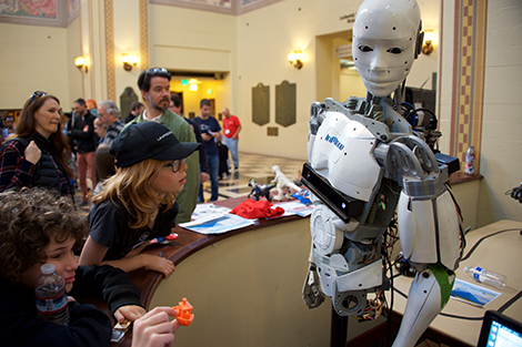 Kids and adults admiring robot