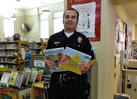 Officer Joseph Oseguera holding up two books