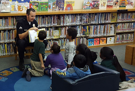 Officer Joe reading to children in the library