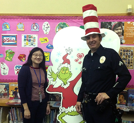 Officer Joseph Oseguera with a librarian wearing a silly hat