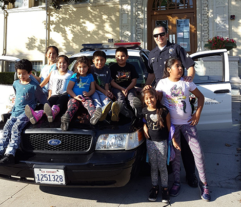 Officer Joe with a group of school kids on his police car
