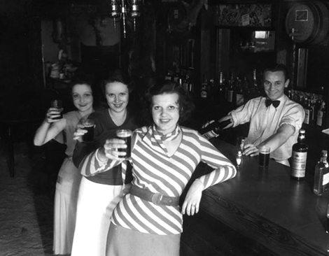 Three women are raising a glass for the photographer as the bartender pours a drink