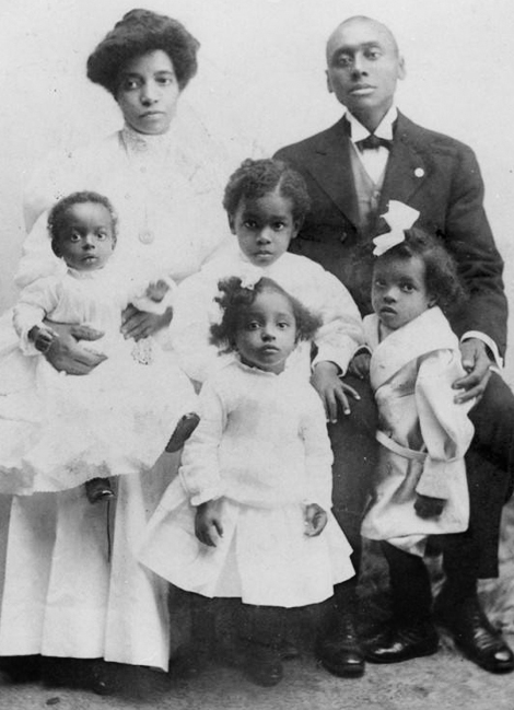 Amanda and Joseph pose with their children Grace, Raymond, Mildred, and Alphonso for a formal family portrait taken in 1907