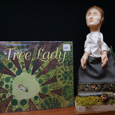 the book The Tree Lady next to a puppet of a character from the book