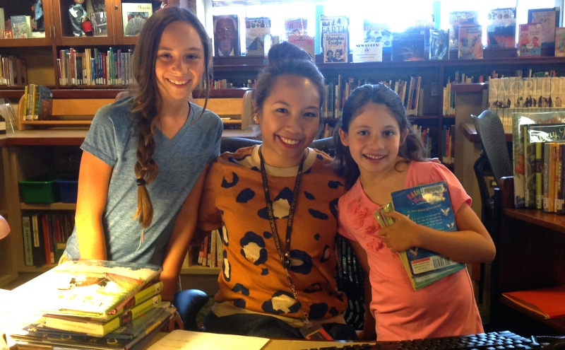 Librarian Joanna Fabicon with young patrons Emily and Adriana.