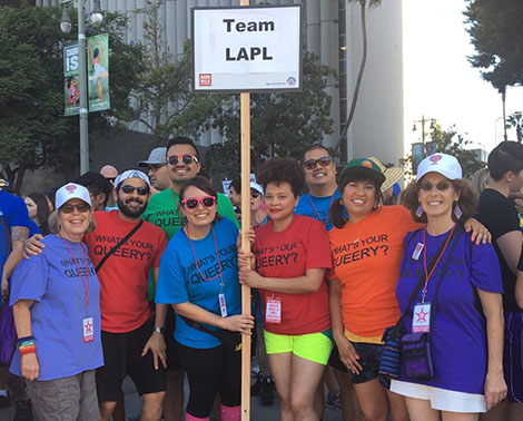 A group of eight Los Angeles Public Library staff members smiling and holding a TEAM LAPL banner at the L.A. AIDS Walk