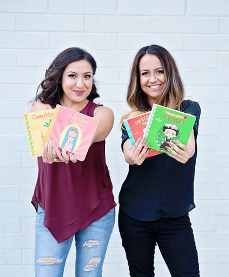 The authors and publishers of Lil Libros, left to right Ariana Stein and Patty Rodrguez. Two women standing side by side wearing jeans and a t-shirt, smiling holding up their books