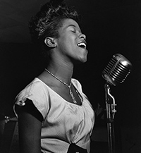 a side profile black and white photo of a young singing and smiling Sarah Vaughan