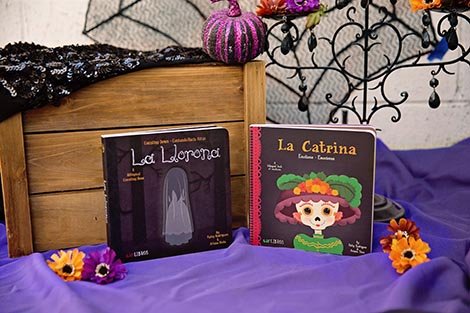 a halloween and dia de los muertos display with two lil libros board books pictured: La Llorona and La Catrina