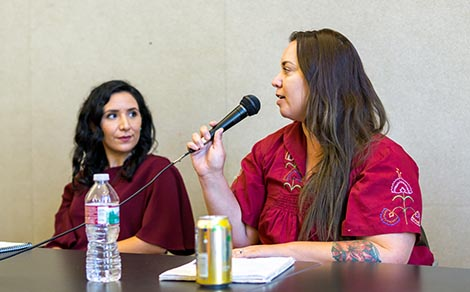 Left to Right, Darlene Stephanie and Alana Medina.  Alana is sitting at a table speaking with a microphone in her hand. Darlene is turned to the right listening to Alana