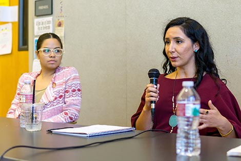 Left to Right Natalie Marrero and Darlene Stephanie.  Darlene is speaking looking ahead with a microphone in her hand, sitting at a table. Natalie is turned to the right, sitting at the same table looking at Darlene.