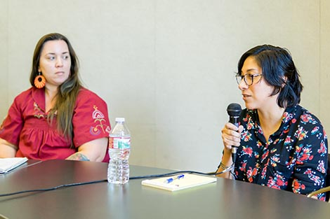 Left to Right, Alana Medina and Mayra Villegas. Mayra is sitting at a table looking ahead while speaking with a microphone in her hand.  Alana is turned to the right looking at Mayra.