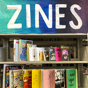 zine sign, and zines on a shelf