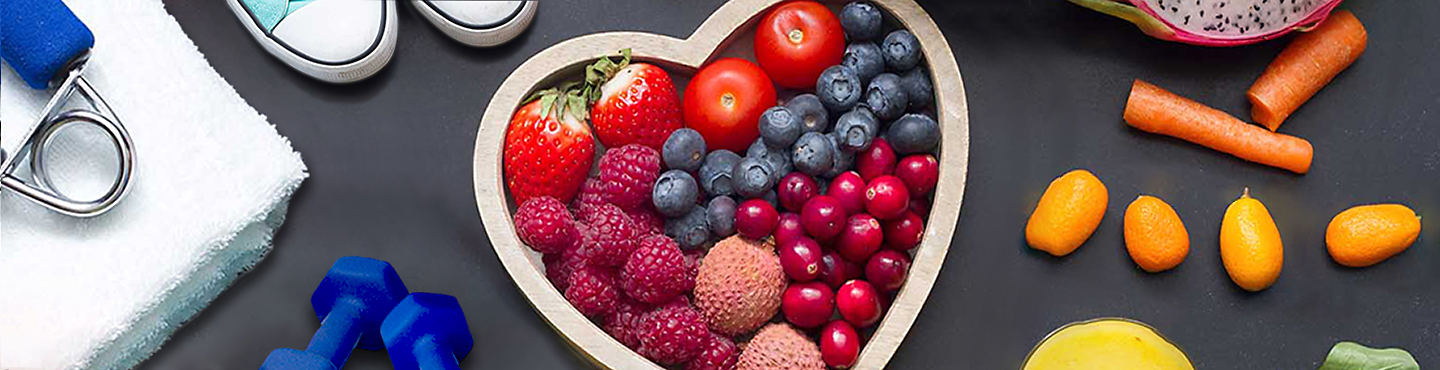 fruit arranged in a heart, vegetables, and exercise equipment for healthy living