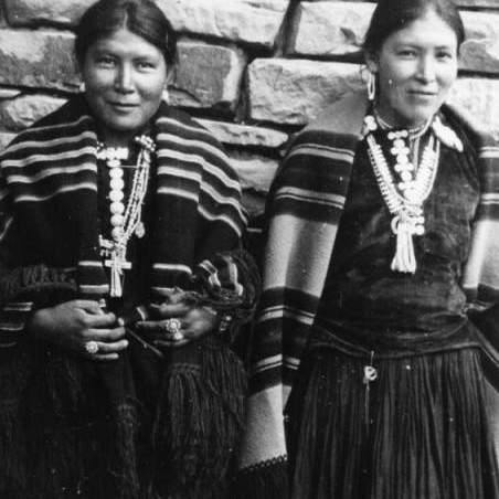 Two Navajo women standing wearing long dresses and silver necklaces smiling, circa 1935