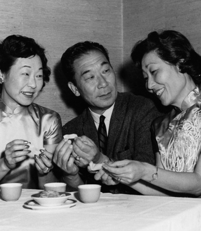 At his Moongate Restaurant, actor Philip Ahn enjoys tea and cookies with his sisters Soorah (left) and Susan, both in silk Chinese dresses.
