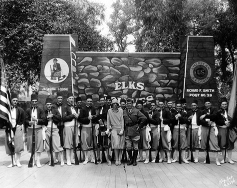 "Group photo of Amelia Earhart with the Championship ""Zouaves"" Elks Drill Team from Jackson, Michigan, at the club during a Convention in 1929. Photo dated: March 17, 1930"