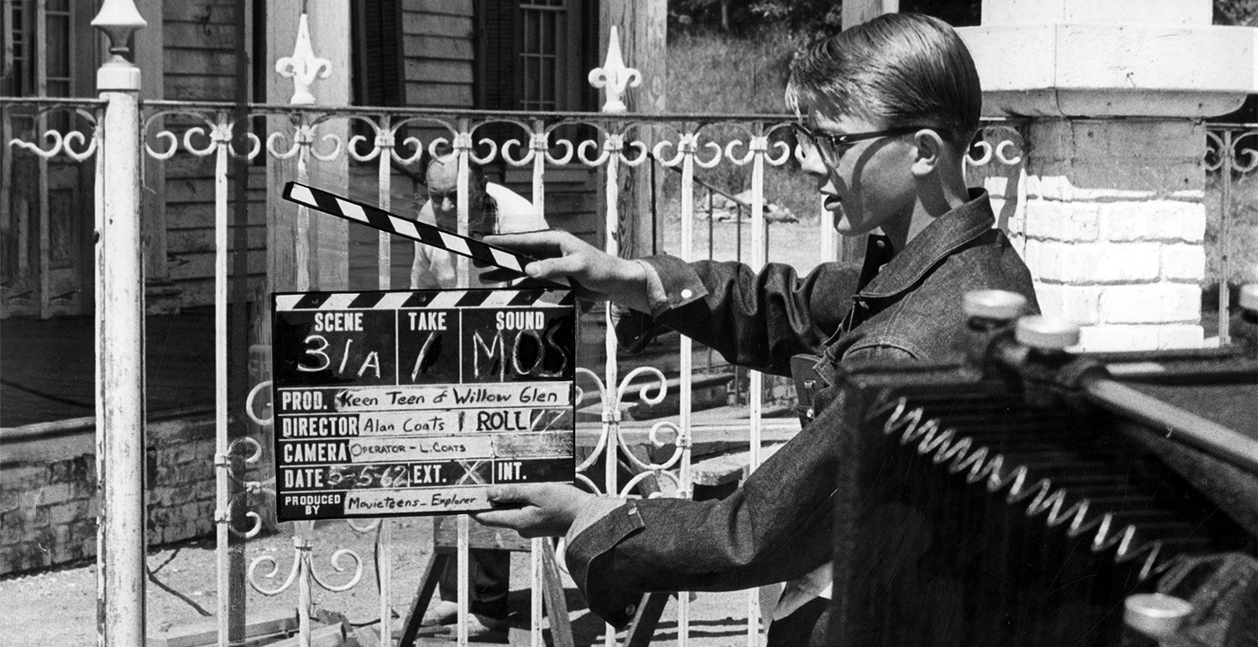 black and white photo of teenager holding a film slate in front of a movie camera