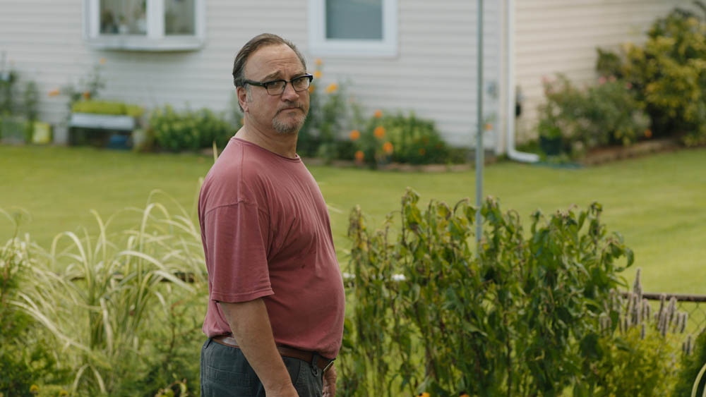 film still of Jim Belushi standing outside next to grass