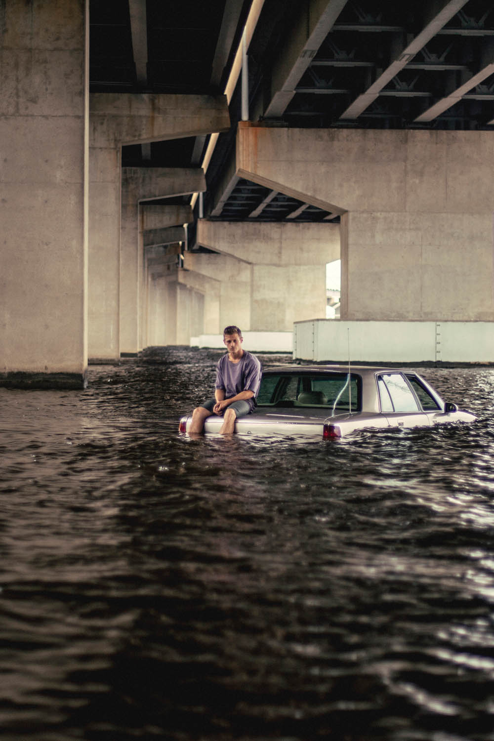 young man sitting on the trunk of a car submerged in a river