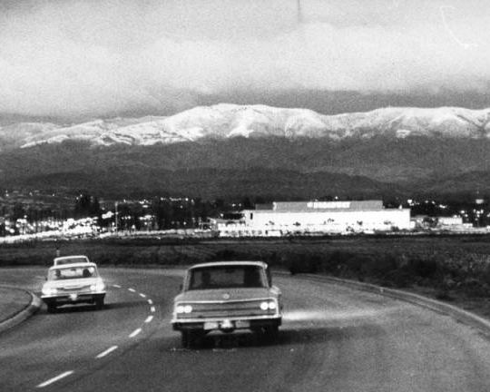 Cars driving on highway with snowy mountains in background.