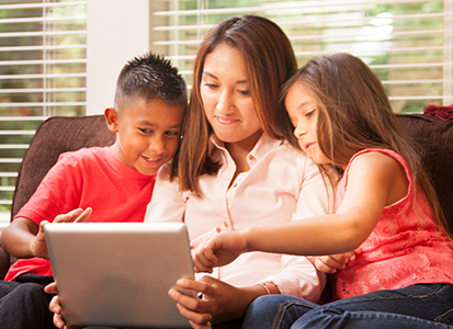 mother watching content from a tablet with her two kids