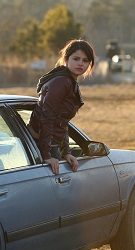 A young woman leans out the open window of the passenger seat of a car.